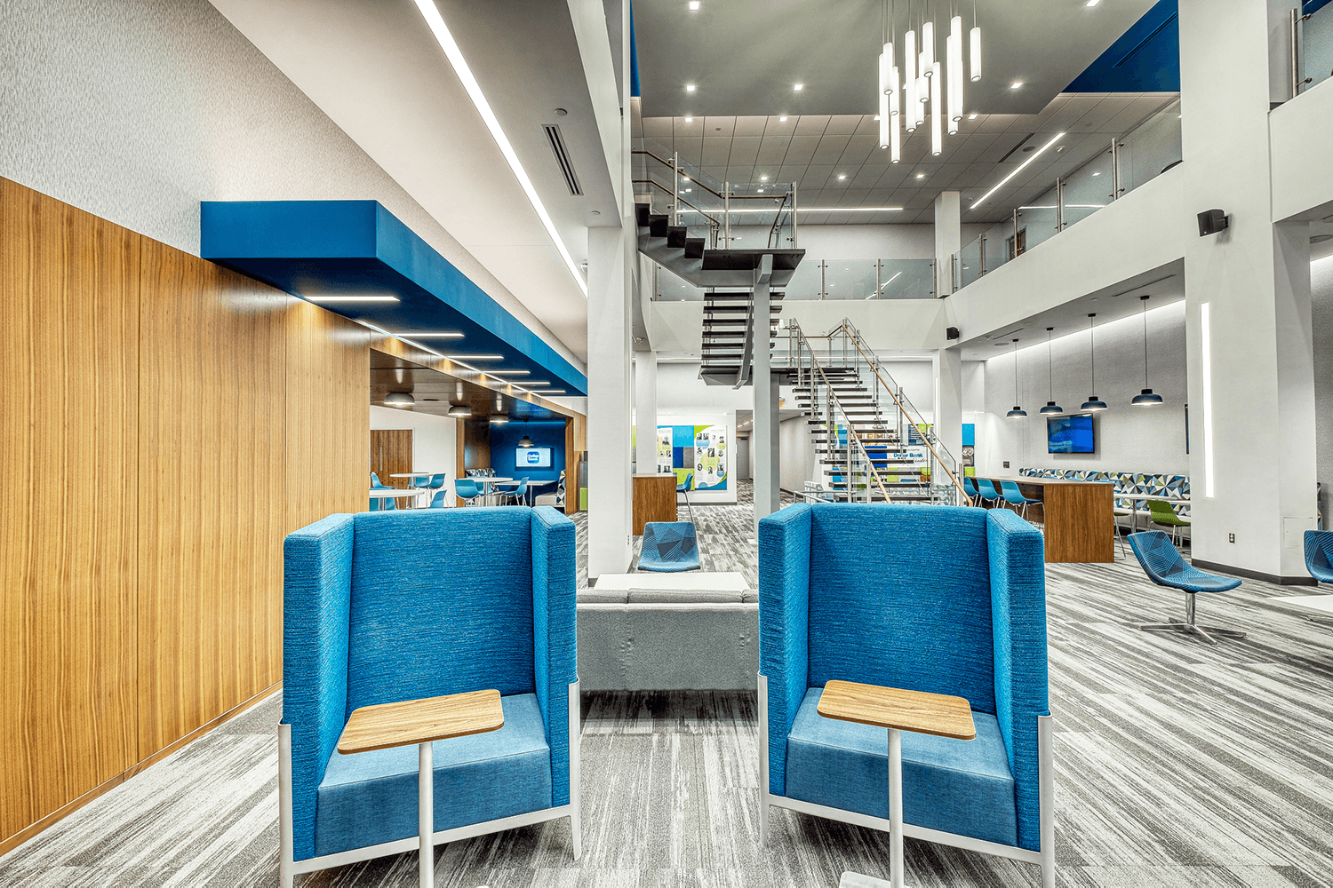 two blue chairs with small mobile desks sitting in front of them