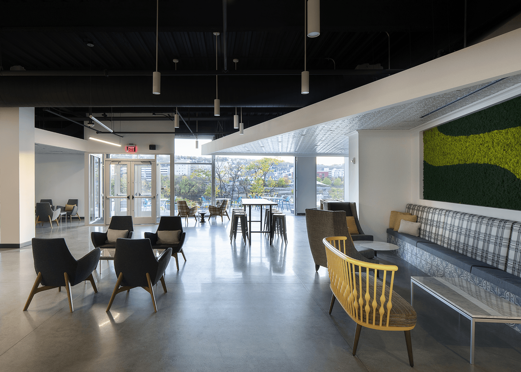 Collaborative space with chairs, tables, and a bay door to outside